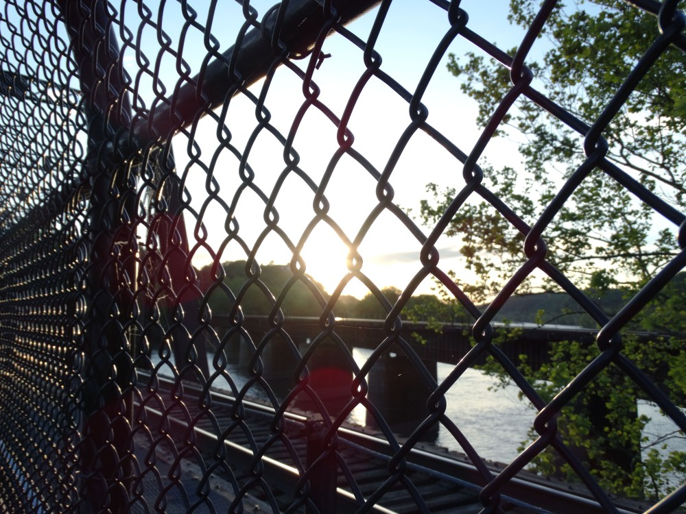 Image of a chain fence with a river, trees, railroad, and the sun visible through the fence.