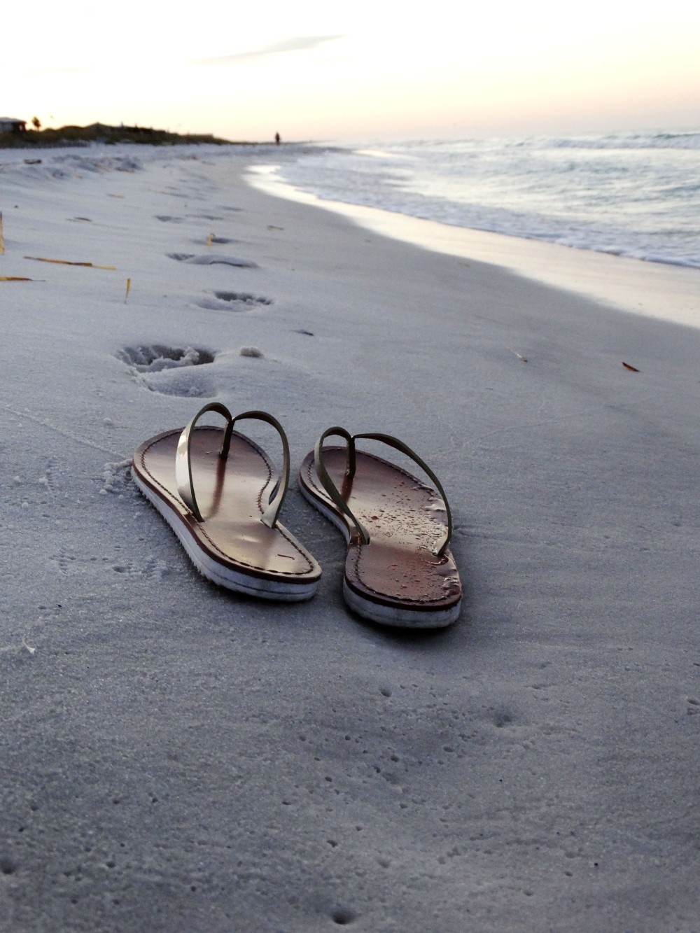Image of a pair of flip flops in the sand behind multiple footsteps next to the ocean. The sunrise is visible in the background.