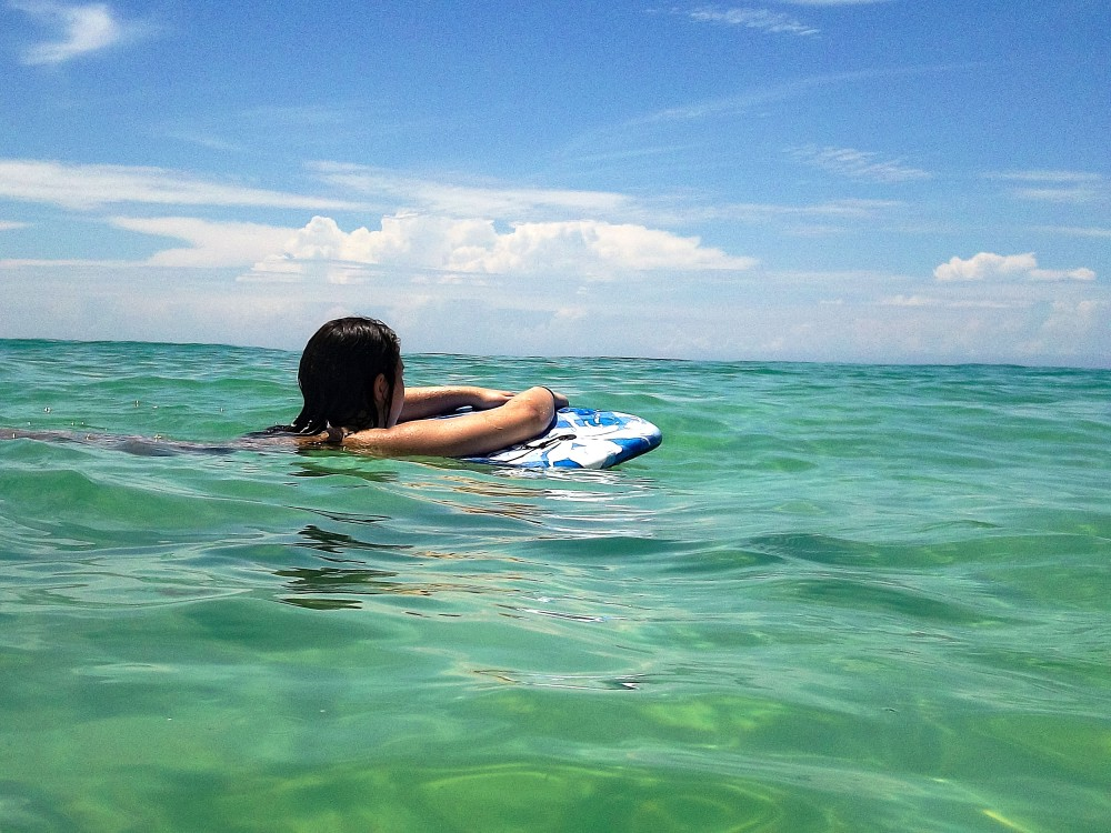 Photo of Kristen Uppercue leaning on a boogie-board and looking off into the distance in the middle of the ocean.