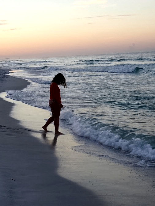 Photo of Kristen Uppercue walking into the ocean.