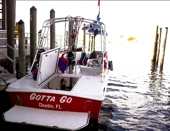 Photo of a boat with the text, Gotta Go Destin, Florida, which was sitting next to a dock.