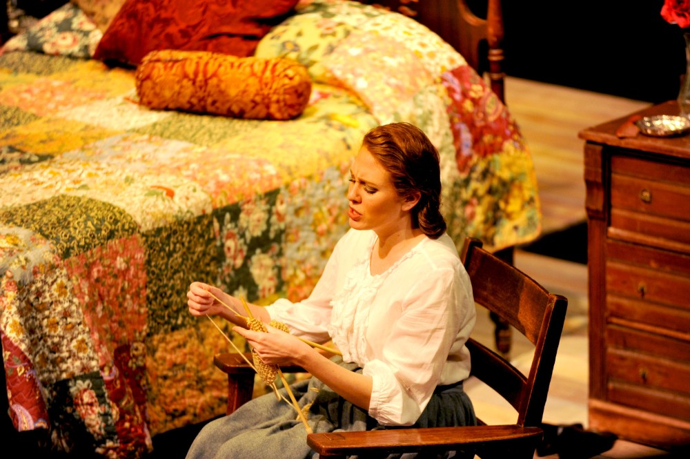 Image of Elizabeth Vaughn knitting during the second play performed of the night, Valentine's Day.